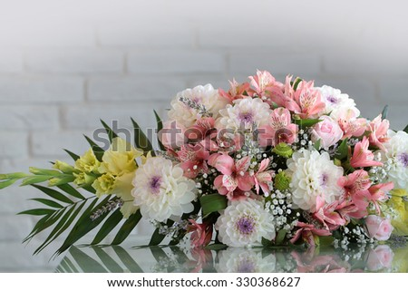Closeup beautiful bunch of fresh tender flowers in white and rosy colores yellow gladioluses mixed decorated with green leaves lies sidelong on glass table on blurred gray background, horizontal
