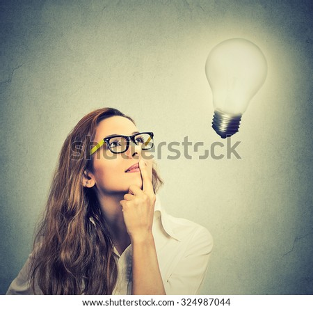 Closeup beautiful girl thinks looking up at bright light bulb isolated on gray wall background. Idea, business, education and people concept. Face expression   - stock photo