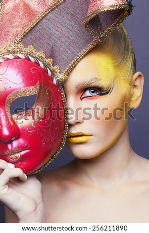 Closeup beautiful portrait of a young cute girl over grey background. Perfect bright makeup. Woman with  yellow lips and Venetian mask. Blonde.