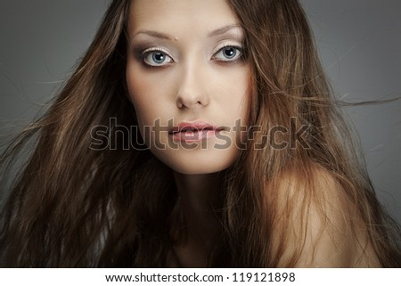 closeup beautiful woman face portrait over gray background with flying hair