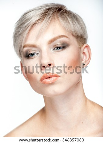Closeup beauty portrait of a young platinum blonde short-haired woman with warm makeup