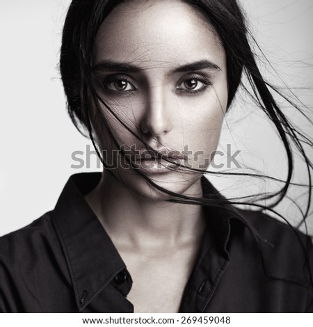 Closeup beauty portrait of a young sensual beautiful brunette girl with long black straight flying hair. Smoky eyes. - stock photo