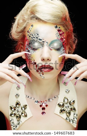 Closeup beauty portrait of attractive model face with bright rhinestones visage.Woman with eye closed.