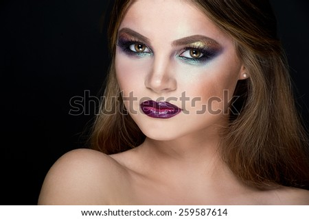 Closeup beauty portrait of attractive model face with bright visage. Multicolored eye makeup and vinous lips make-up  - stock photo