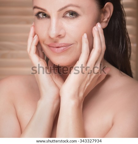 Closeup beauty portrait of attractive natural brunette woman. Woman looking at camera, holding hands on face. Cute smile. - stock photo