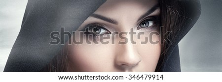 Closeup beauty portrait of attractive young woman with beautiful brown eyes. Hood on head. Brunette girl. Studio shot. - stock photo