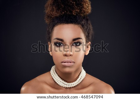 Closeup beauty portrait of elegant african american girl wearing pearls. Glamour makeup. Creative hairstyle.