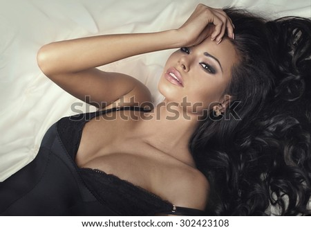 Closeup beauty portrait of sexy brunette woman with big brown eyes, perfect makeup and long hair. Girl lying in bed, relaxing.