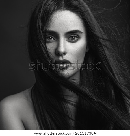 Closeup beauty portrait of young beautiful brunette girl with long black straight flying hair. Black and white.
