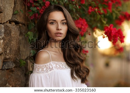 Closeup beauty portrait of young pretty girl with dark curly hair looking at you. Soft sunset backligth - stock photo