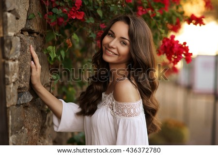 Closeup beauty portrait of young pretty happy smiling girl with dark curly hair looking at you. Soft sunset backligth