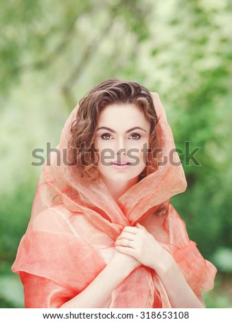 Closeup beauty portrait of young white Caucasian girl with hazel eyes, wavy curly hair covered with red orange pastel hood clothes gauze, in park outside on summer day, on green background. - stock photo