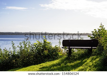 Closeup bench close to the beach and the water - stock photo