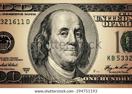 closeup Benjamin Franklin face on the US $100 dollar bill.
