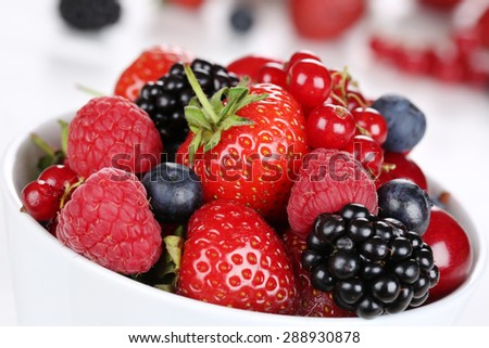 Closeup berry fruits in bowl with strawberries, blueberries, red currants, cherries, raspberries and blackberries - stock photo