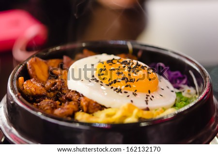 closeup bibimbap with fried egg in a heated stone bowl ,  korean style food - stock photo
