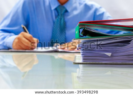 closeup binder on desktop and blurred businessman writing document data - stock photo