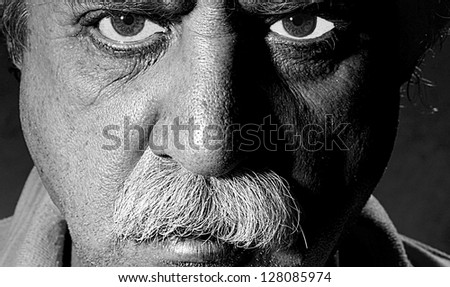 Closeup black and white character portrait of a man with blue eyes looking at the camera with questioning and suspicious facial expression