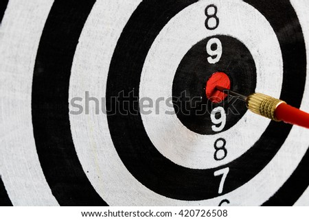 Closeup black and white dartboard in the red center with selective focus.Success hitting target aim goal concept background.