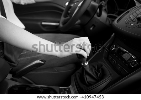 Closeup black and white photo of female driver shifting gear stick