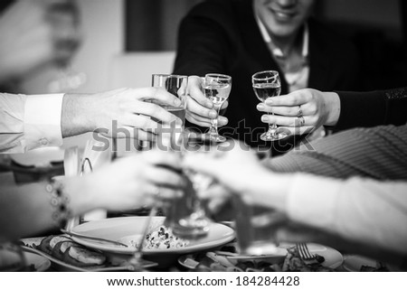Closeup black and white photo of hands clinking glasses at restaurant - stock photo