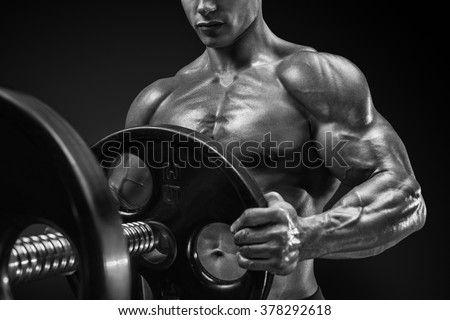 Closeup black and white photo of handsome bodybuilder guy prepare to do exercises with barbell in a gym, keep barbell plate in hands - stock photo