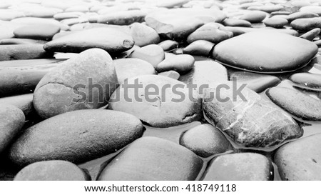 Closeup black and white photo of stones lying in river - stock photo