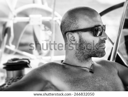 Closeup black and white portrait of sexy handsome man relaxing on sailboat, wearing stylish sunglasses, fashion and vogue concept - stock photo