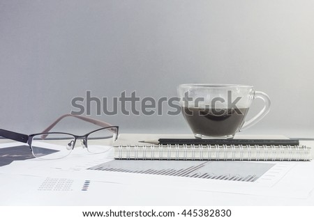 Closeup black coffee in cup of coffee on note book and pencil with work paper on blurred wooden desk and glass wall textured background , work concept by coffee work paper and eyeglasses in art tone