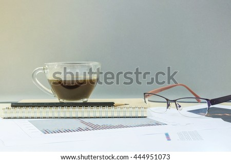 Closeup black coffee in transparent cup of coffee on note book and pencil with work paper on blurred wooden desk and glass wall textured background , work concept by coffee work paper and eyeglasses