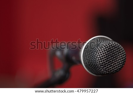 Closeup black vocal microphone mounted on mic stand, blurry red dark bcakground