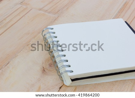 closeup blank notebook on a brown wooden table, copyspace - stock photo