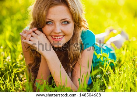 closeup blonde woman lying on grass at park