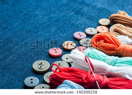 Closeup blue jeans background with different buttons and threeds. Space for your text. - stock photo
