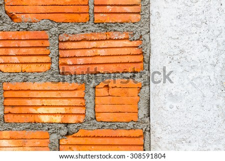 closeup brick wall with wet layer concrete and dry white wall on the right - stock photo
