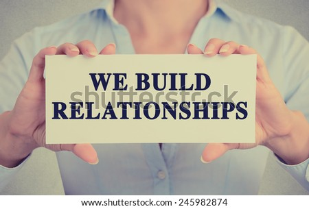 Closeup business woman hands holding white card sign with we build relationships text message isolated grey wall office background. Retro instagram style image. Human communication leadership concept  - stock photo