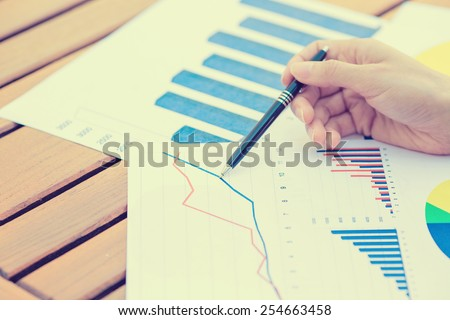 Closeup business woman hands with pen presenting company annual report statement document, papers chart, growing up graph. Stock market, office, tax, education concept. - stock photo