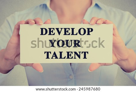Closeup businesswoman hands holding white card sign with develop your talent text message isolated on grey wall office background. Retro instagram style image - stock photo