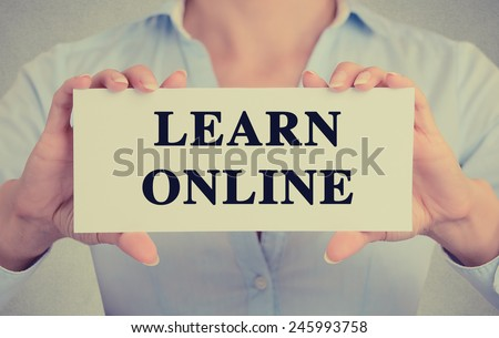 Closeup businesswoman hands holding white card sign with learn online text message isolated on grey wall office background. Retro instagram style image. Globalization education technology concept  - stock photo