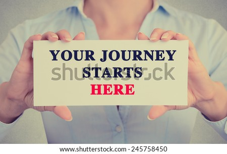 Closeup businesswoman hands holding white card sign with Your Journey Starts Here text message isolated on grey wall office background. Retro instagram style image - stock photo