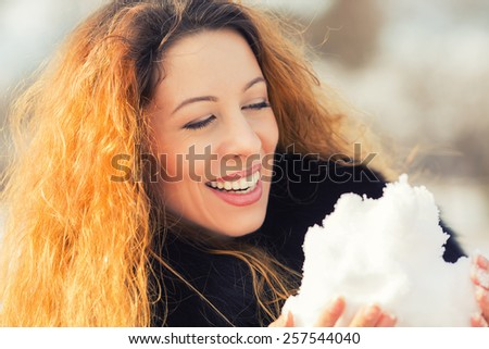 Closeup carefree woman with long curly hair playing with snow in park on a sunny day. Positive face expression emotion  - stock photo