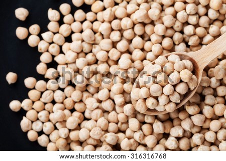 Closeup chickpea in wooden spoon and heap chickpea scattered on black background, top view