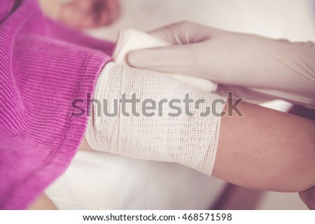 Closeup child injured. Pediatrician doctor bandaging child's knee. Shallow depth of field (DOF), selective focus, bandage in focus. Human health care and medicine concept. Vintage tone effect.