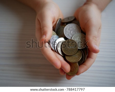 closeup child's hands holding world coins isolated on white background, human hands and saving concepts