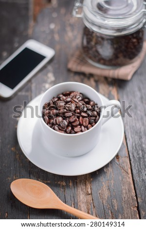 Closeup coffee bean in a  cup on wooden table , selective focus  - stock photo