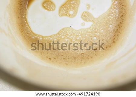 closeup Coffee foam at bottom of cup.