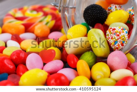 Closeup colorful candies in jar. Candies scattered on the wooden table - stock photo