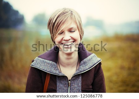 Closeup colorful portrait of young happy laughing girl - stock photo