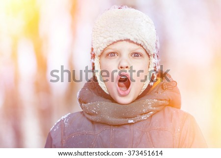 Closeup colorful winter portrait of young shouting boy in hat, scarf and jacket at outdoors sunny background. - stock photo