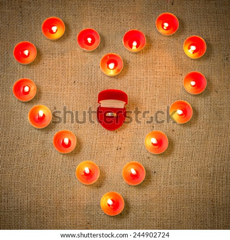 Closeup conceptual photo of wedding ring surrounded by candles in shape of heart - stock photo